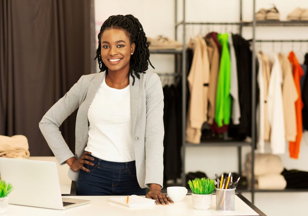Cheerful Shop Assistant Girl Smiling Standing In Clothing Store